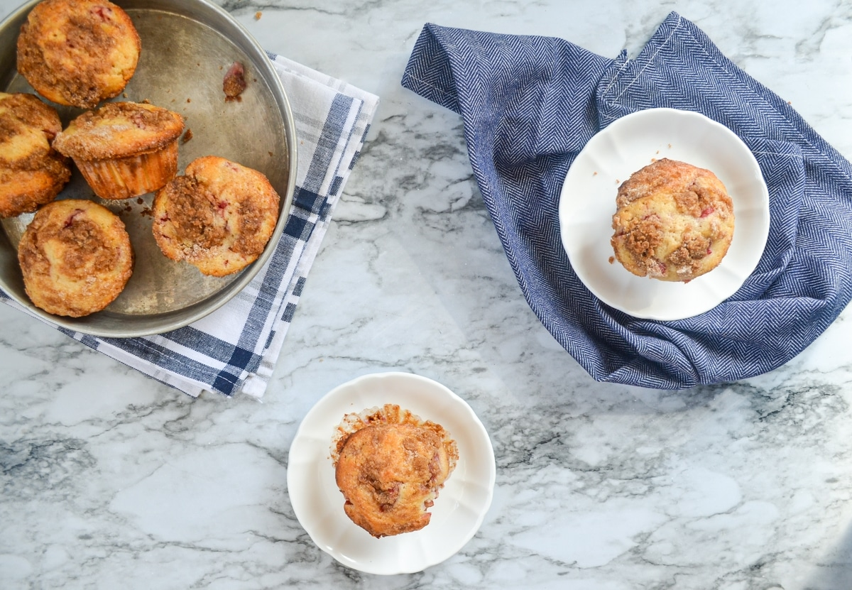 An overhead view of strawberry buttermilk muffins. One is on a white plate on the counter, another on a white plate on a napkin, and a few more in a pan to the left hand side.