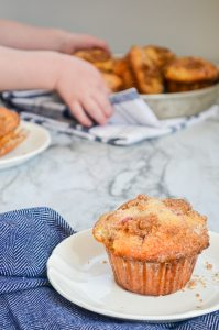 A strawberry buttermilk muffin on a white plate, resting on a blue napkin. In the background, a child lifts up a tray of muffins.