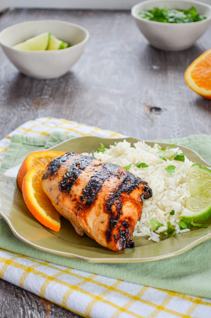 A plate of grilled chicken, garnished with an orange wedge and served with rice.