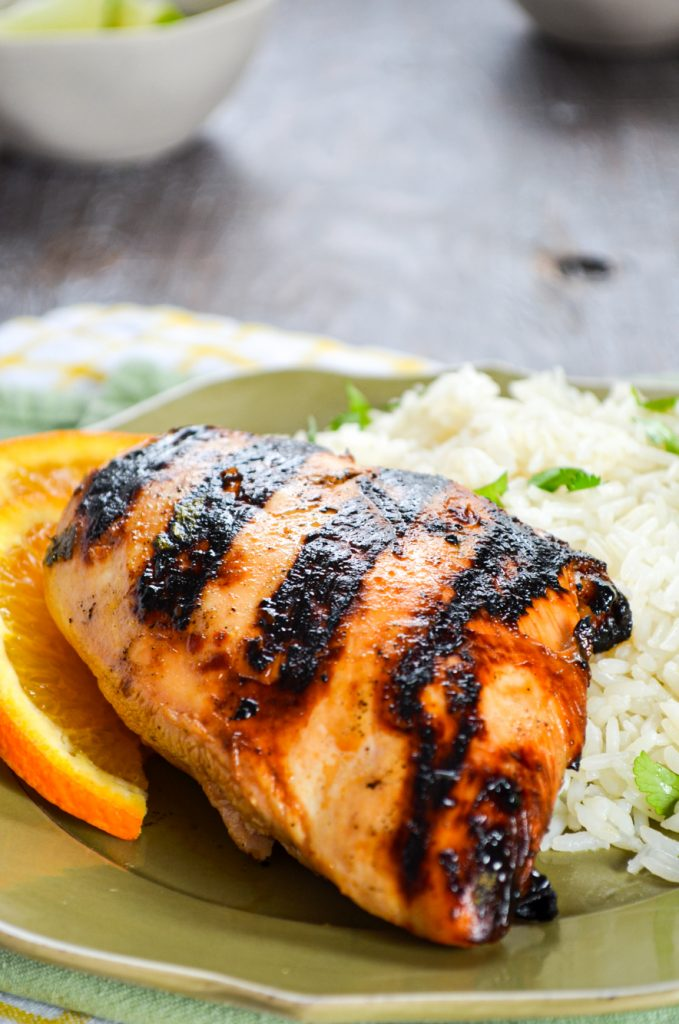 A close up of Grilled chicken on a bed of white rice.