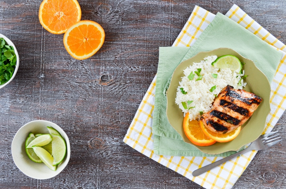 A plate of grilled chicken, served with some rice on the side. Garnish of cilantro, lime wedges, and orange wedges.