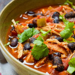 A bowl of chicken taco soup, garnished with cilantro.