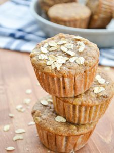 A stack of three muffins with oats sprinkled on top.