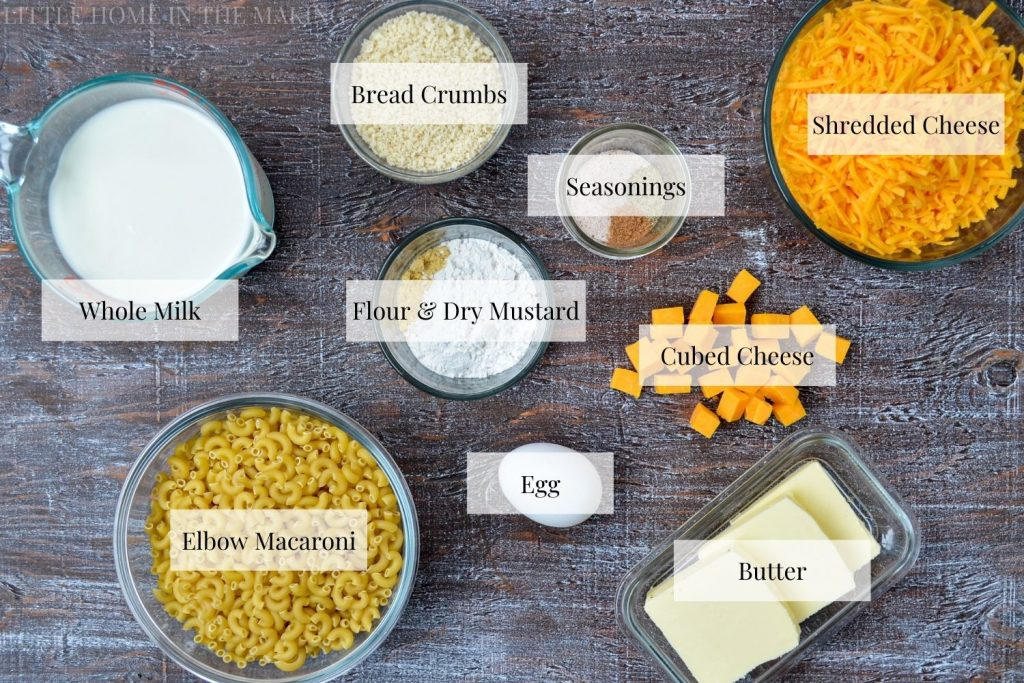 All of the ingredients needed to make macaroni from scratch: cheese, seasonings, flour, mustard powder, breadcrumbs, butter, egg, macaroni, and milk.
