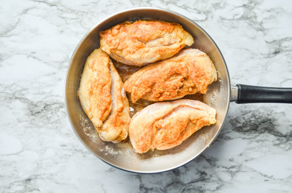 Chicken breasts cooked in a skillet with butter.