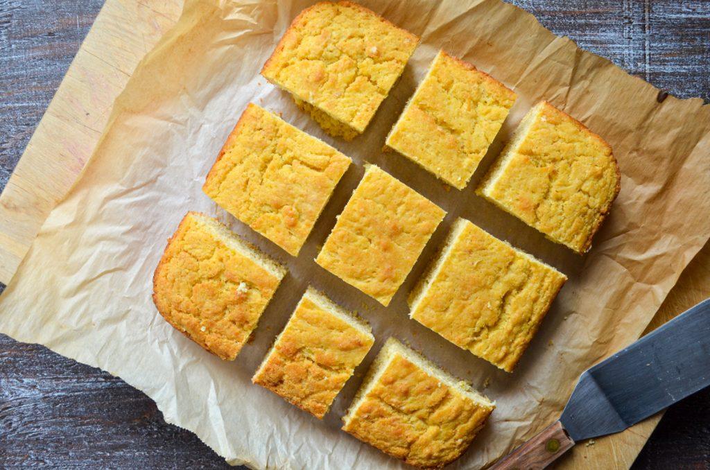 An overhead view of sourdough cornbread, cut into 9 squares.