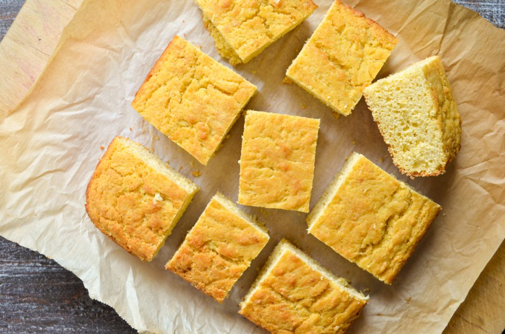 9 squares of baked cornbread on a piece of parchment paper.