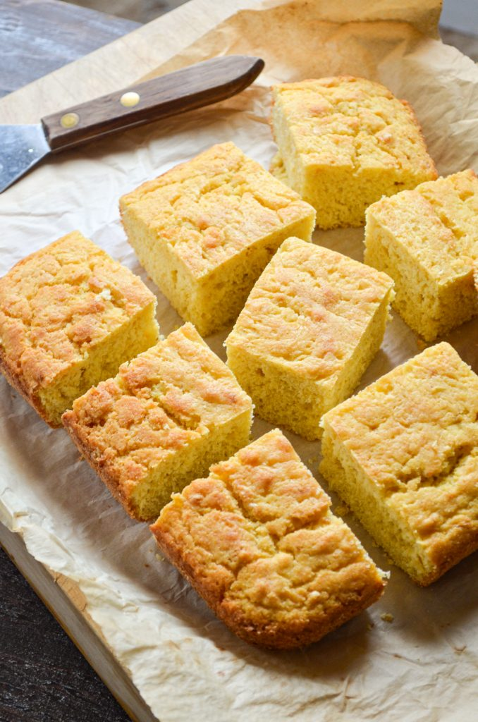 Cornbread on a parchment lined cutting board, cut into 9 pieces.