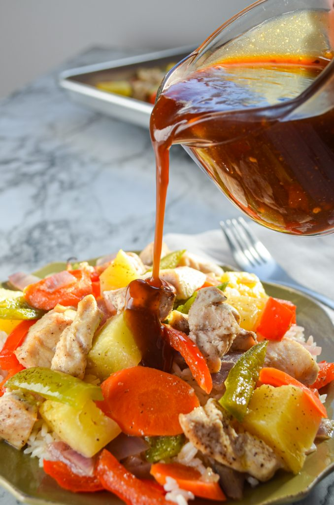Sweet and sour sauce being poured on a dish of chicken and vegetables.