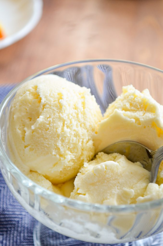 Several scoops of orange creamsicle ice cream in a small glass bowl.