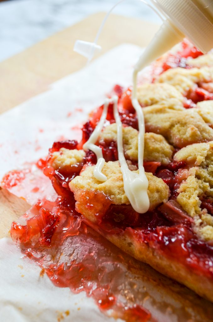A strawberry crumb bar being drizzled with icing.
