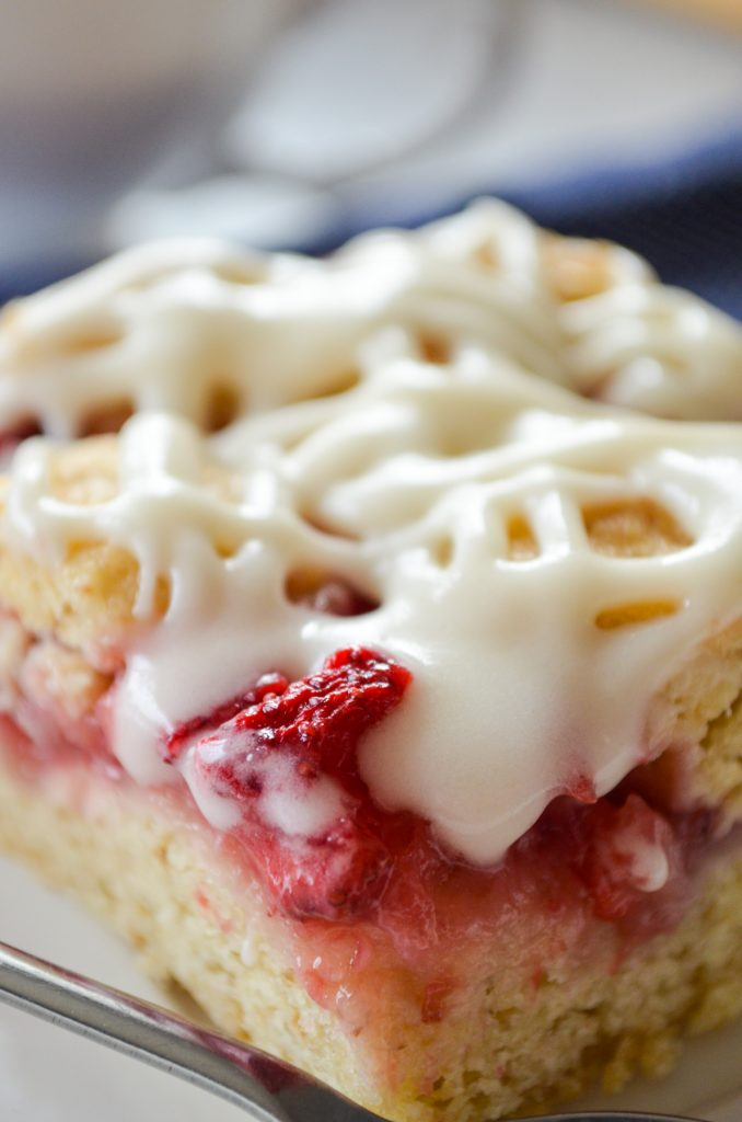A big slice of strawberry oatmeal crumb bar, with a icing drizzle on top.