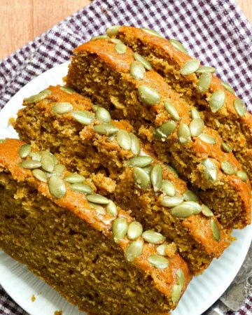 Slices of sourdough pumpkin loaf, sprinkled with pepitas.