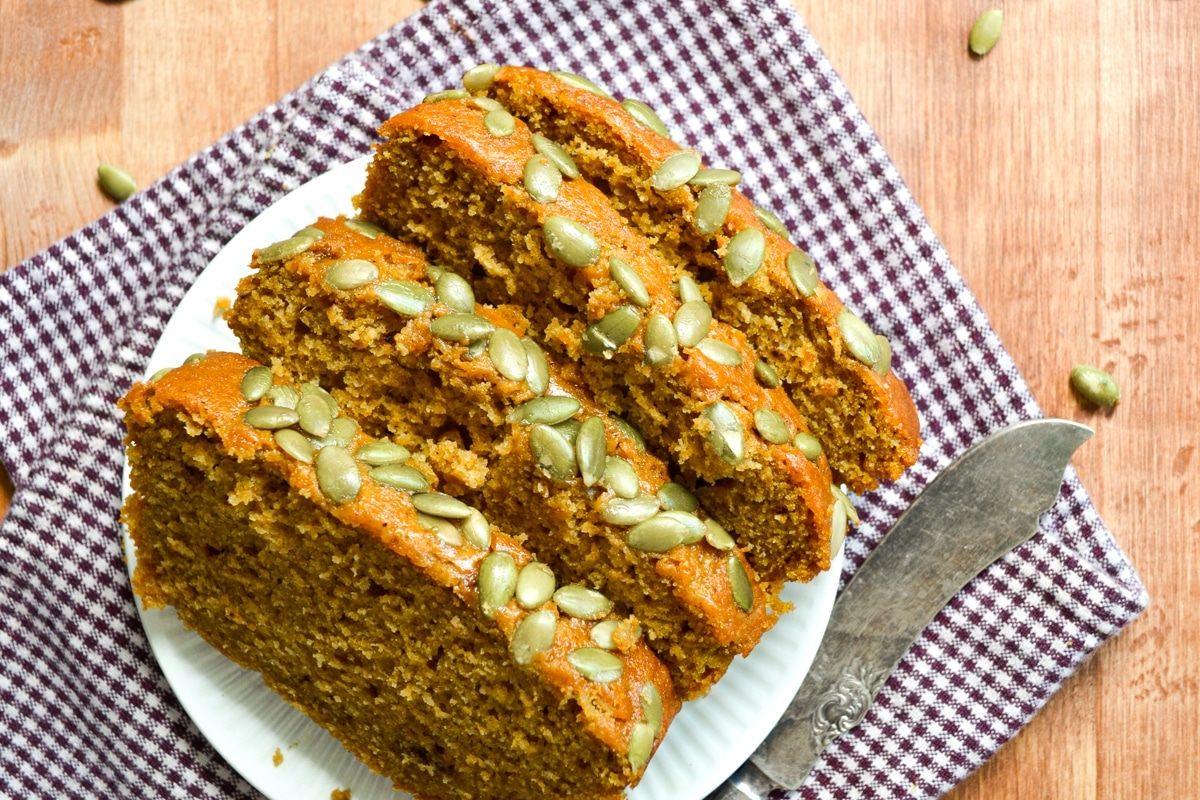 Several slices of pumpkin loaf, topped with pepitas.