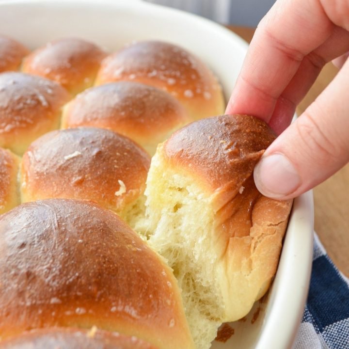 A warm baked roll being pulled out of a baking dish.