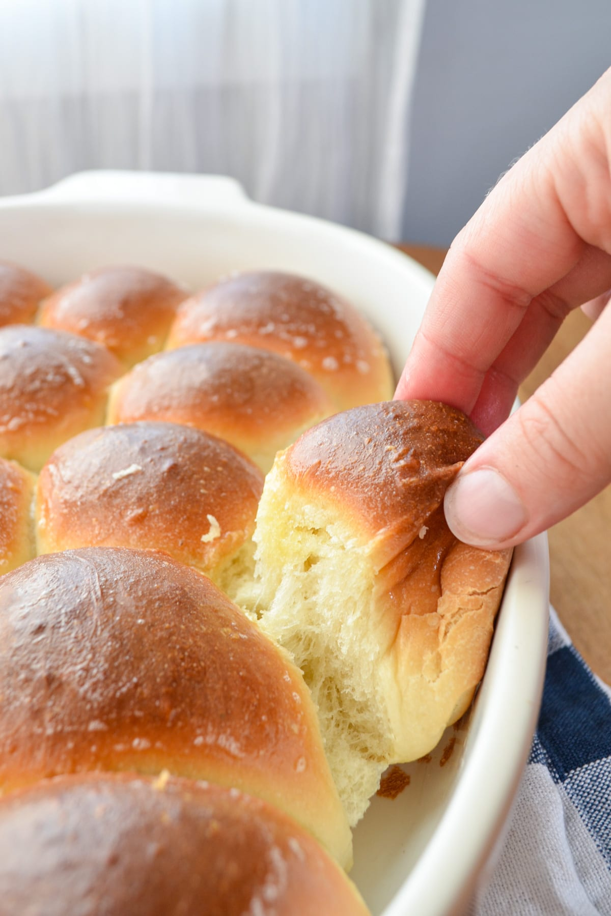 A soft and fluffy snowflake roll being pulled from a baking dish.