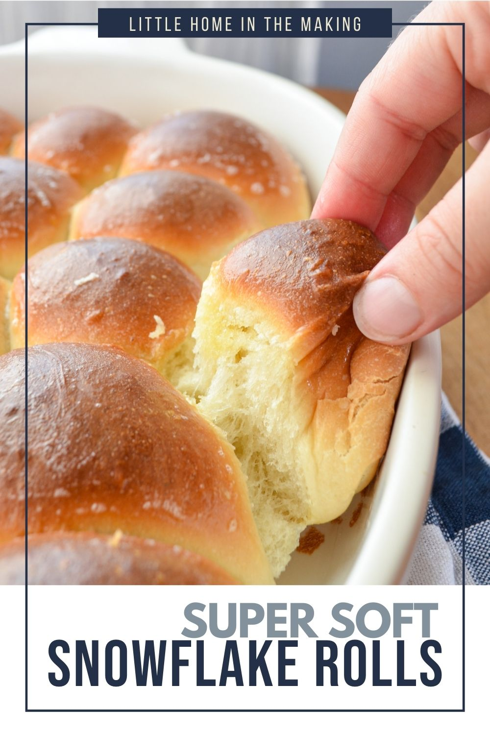 A soft dinner roll being pulled from a baking dish.